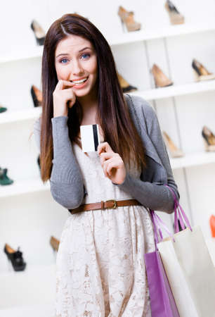 doubtfulness: Woman keeps credit card in footwear shop with great variety of stylish shoes