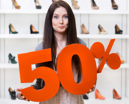 Woman keeps the model of 50% sale on footwear standing at the shopping center against the showcase with pumps photo