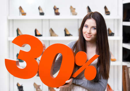 Woman keeps the model of 30% sale on shoes standing at the shopping center against the showcase with pumps photo
