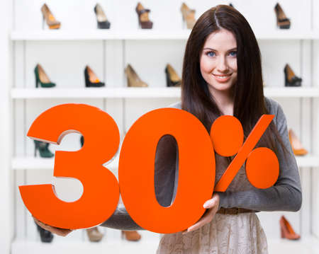 Woman keeps the model of 30% sale on footwear standing at the shopping center against the showcase with pumps photo
