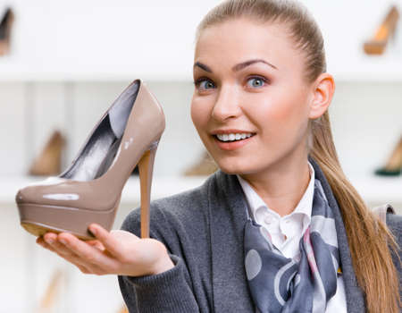 heeled: Portrait of woman keeping coffee-colored shoe in shopping center against the showcase with shoes Stock Photo