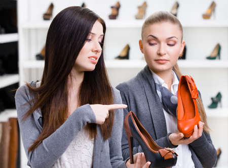 Shop assistant offers stylish pumps for the female customer in the shopping center photo