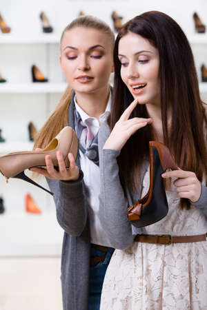 Shop assistant offers footwear for the female customer in the shopping center photo
