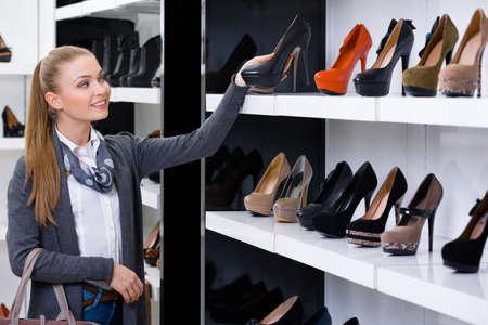 tienda zapatos: Una mujer mirando a las filas de los zapatos en el centro comercial Foto de archivo