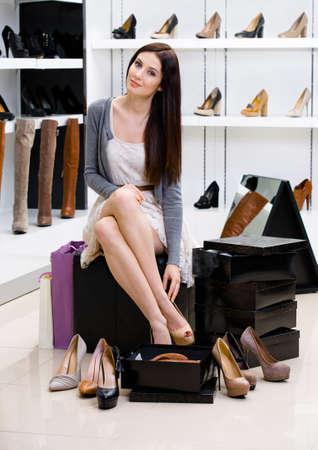 Frau sitzt auf dem Stuhl und versucht auf Schuhe im Shop kann sich nicht entscheiden, was zu kaufen