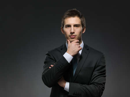 half-length portrait of pensive man wearing business suit and black tie touches his face photo