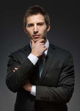 half-length portrait of pensive business man wearing business suit and black tie touches his face photo