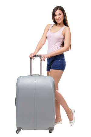 Full-length portrait of female tourist with silver travel suitcase wearing shorts and T-shirt, isolated on white photo