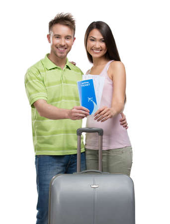 Portrait of embracing couple with suitcase and tickets, isolated on white. Concept of romantic vacations and lovely honeymoon photo