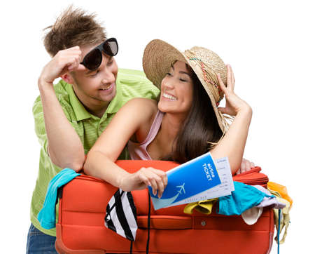 Couple packs suitcase with clothing for travel, isolated on white. Concept of romantic vacations and lovely honeymoon