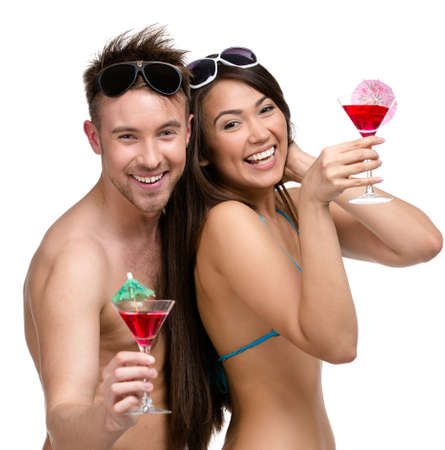 Half-length portrait of half-naked couple with cocktails, isolated on white. Concept of romantic vacations and lovely honeymoon photo