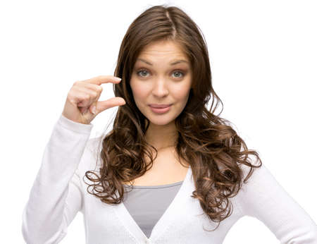 Portrait of woman showing small amount of something, isolated on white