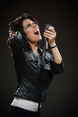 Half-length portrait of female rock musician wearing black jacket and holding microphone on grey background. Concept of music and rave photo