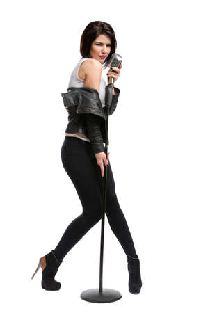 Full-length portrait of rock musician wearing leather jacket and keeping static mic, isolated on white. Concept of rock music and rave photo