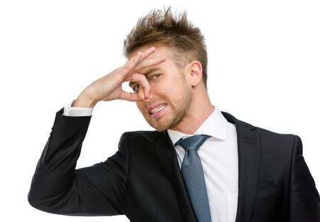 Half-length portrait of manager covering his nose, isolated on white. Concept of stink and disgust Stock Photo