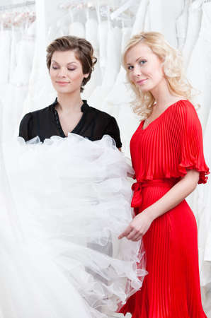 Two girls stare at the wedding dress hesitating about fitting, white background photo