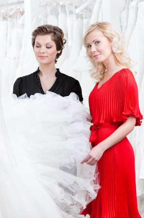 hesitating: Two girls stare at the wedding dress hesitating about fitting, white background Stock Photo