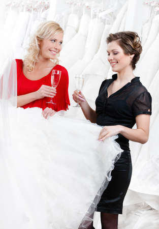 Two girls drink champagne while discussing and choosing the wedding gown photo