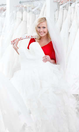 Bride wishes to try wedding dress on, on white background photo