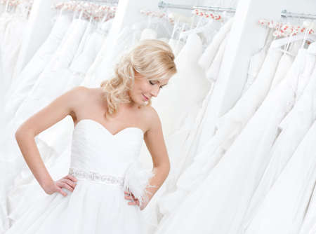 Youg girl is trying on an amasing wedding gown, white background photo