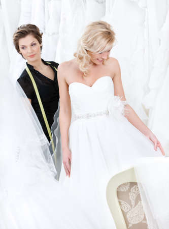 Girl admires the wedding dress that suits her photo