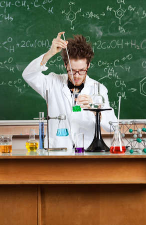 conducts: Mad professor conducts some chemical experiments in his laboratory