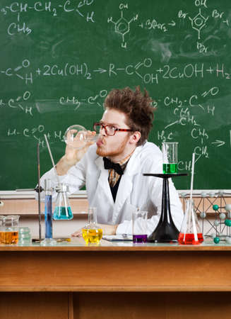 Mad professor drinks the liquid in the vial in his laboratory Stock Photo
