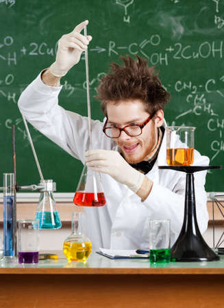 Mad professor adds something to the Erlenmeyer flask with red water Stock Photo - 27732922