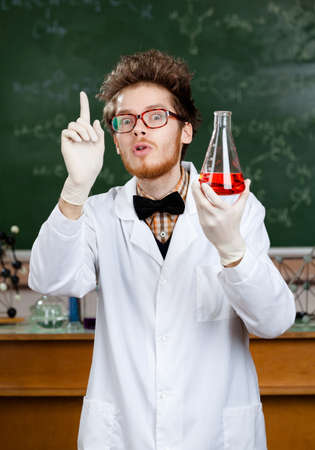 Mad professor in rubber gloves and spectacles works in his laboratory