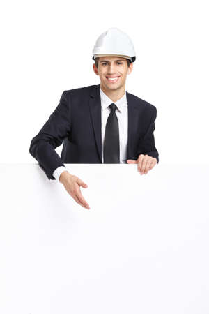 architecting: Businessman in white hard hat pointing hand gestures at copyspace, isolated on white. Concept of success and advertisement