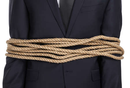 Close up of businessman tied with the rope, isolated on white. Concept of slavery and violence photo