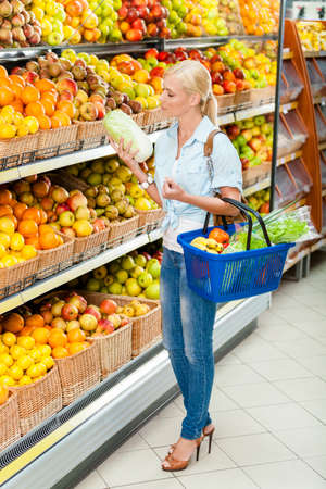 Girl at the shop choosing fruits and vegetables hands cabbage and full of purchases hand cart photo