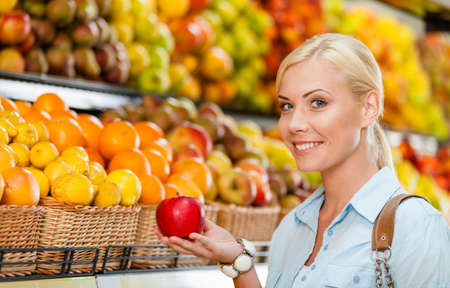 long shot: Girl at the shop choosing fruits and vegetables hands fresh red apple