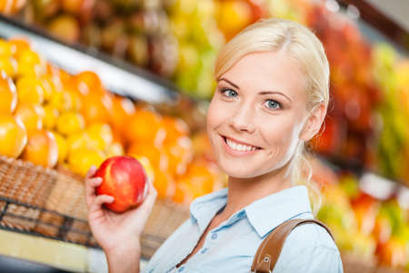 Girl at the shopping mall choosing fruits and vegetables hands fresh red apple photo