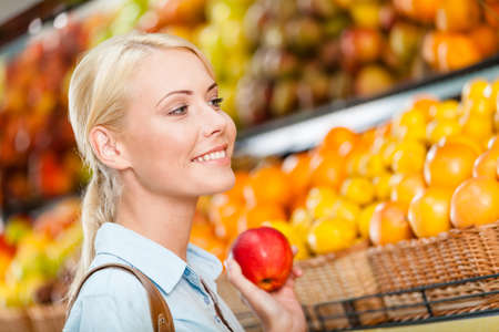 Girl at the store choosing fruits and vegetables hands fresh red apple photo