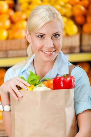 Girl hands paper bag with fresh vegetables against the shelves of fruits in the shop photo