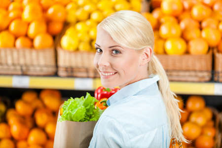 Girl hands paper bag with fresh vegetables against the shelves of fruits in the market photo