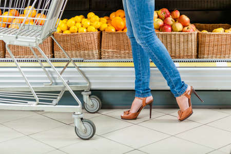 Legs of the female customer with cart against the shelves of fruits in the shop photo