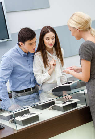 Shop assistant helps couple to select jewelry at jewelers shop. Concept of wealth and luxurious life photo