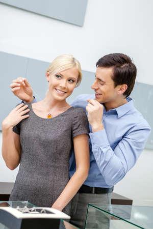 男は、宝石商の店で彼のガール フレンドにネックレスを置きます。富と贅沢な生活の概念