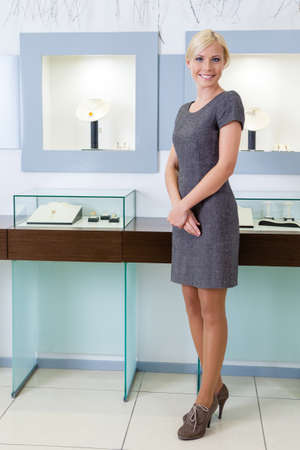 jewel case: Shop assistant stands near the window case at jewelers shop. Concept of wealth and luxurious life Stock Photo