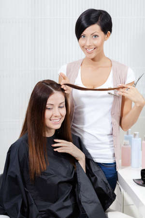 Hair stylist cuts hair of woman in hairdress salon. Concept of fashion and beauty