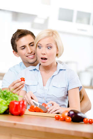 Couple preparing breakfast sitting together at the breakfast table full of groceries photo