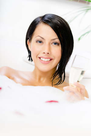 Woman taking a bath with suds and rose petals drinks\ champagne and relaxes