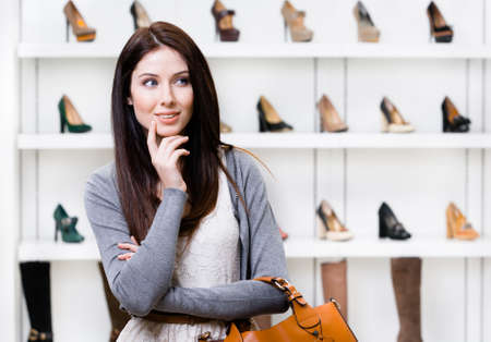 consumerism: Portrait of woman in shopping center in the section of female stylish shoes. Concept of consumerism and stylish purchase