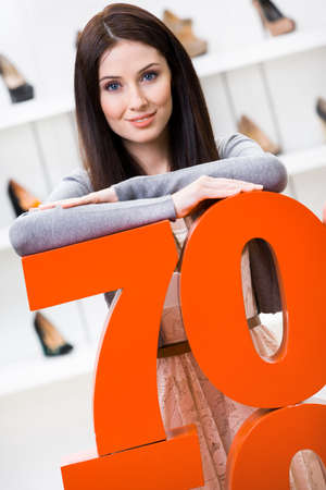 Woman showing the percentage of sales on stylish pumps in the shopping center against the window case with pumps photo