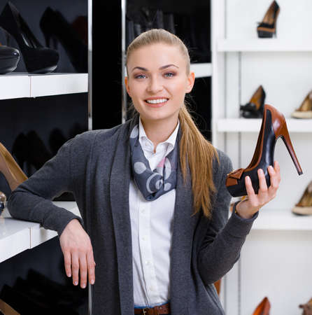 Woman with shoe in hand chooses high heeled shoes looking at the shelves with numerous shoes photo