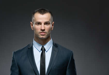 professionalism: Front view of self-confident businessman in dark suit with black tie. Concept of professionalism and success in business Stock Photo