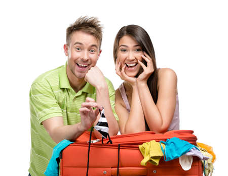 Couple packs suitcase with clothing for journey, isolated on white. Concept of romantic vacations and lovely honeymoon photo