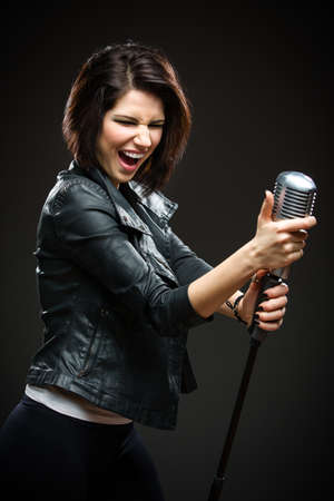 Half-length portrait of female rock singer wearing black jacket and handing mic on grey background. Concept of music and rave photo